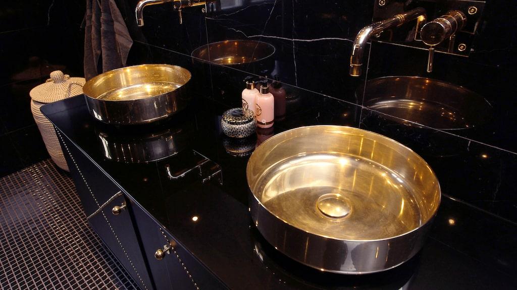 Badrumsskåpet är från 50-talet och inklätt i svart skinn och mässingsnitar från Plan B design. Tvättställ i mässing från Superfront och kranar från Tapwell.