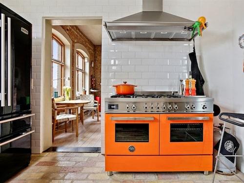 Köket har lyxig inredning, bland annat en orange Bertazzoni gasolspis.