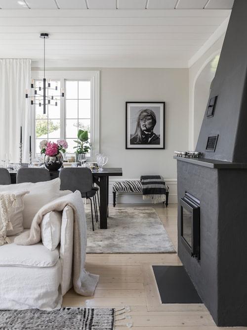 Vardagsrummet är det mest använda rummet i huset med sin imponerande öppna spis. För att få en kontrast mot väggarna i en ljusbeige ton målade Mimmie den öppna spisen mörkt grå. Dessutom framträder elden ännu bättre mot det mörka. Takkrona, Herstal. Tavla, Newport. Matta och bänk, Classic Collection.