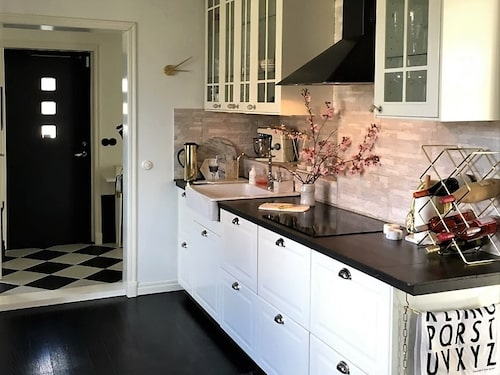 Det nyrenoverade köket går i grafiskt svart och vitt och matchar det schackrutiga hallgolvet.