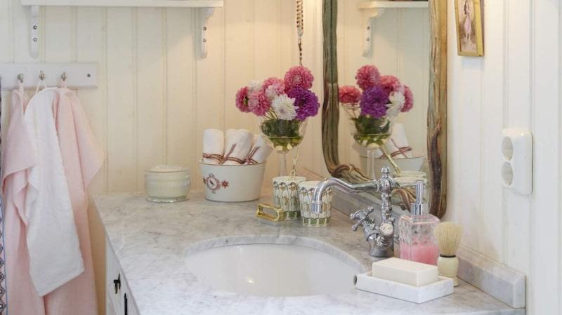 Nyrenoverat i äldre stil. Pärlspont målad krämigt vit. Art deco-spegel köpt i en antikaffär i London. Vägglampor Adelborg i blank mässing, Karlskrona lampfabrik. Badrumsmöbel med underlimmad porslinsvask och bänkskiva av carraramarmor. Tvättställsblandare, båda från Qvesarum.