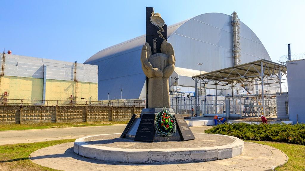 Minnesmärket framför reaktor 4, innesluten i sin nya sarkofag.
