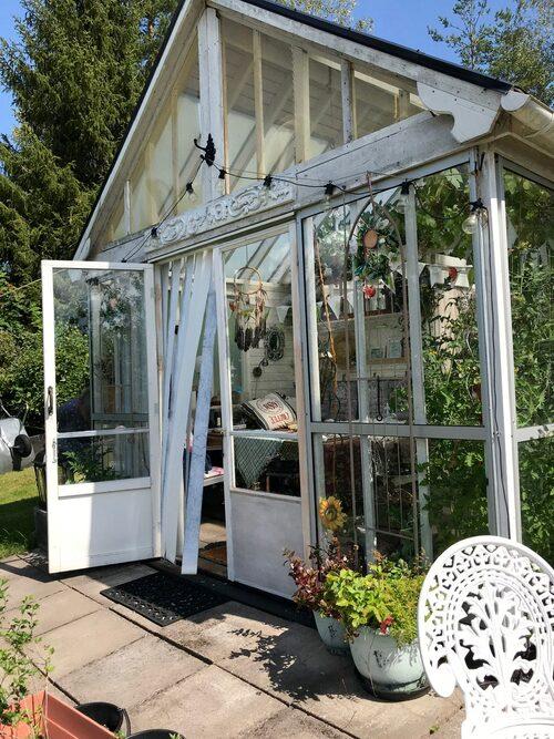 Växthuset på 15 kvadratmeter är byggt av glasdörrar, plank och en gammal enkeldörr som Ann Katrin gjort om till en dubbeldörr.
