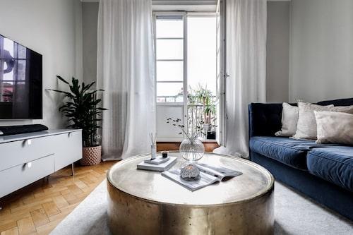 Ljust vardagsrum med fiskbensparkett och gråmålade väggar samt utgång till kungsbalkongen.