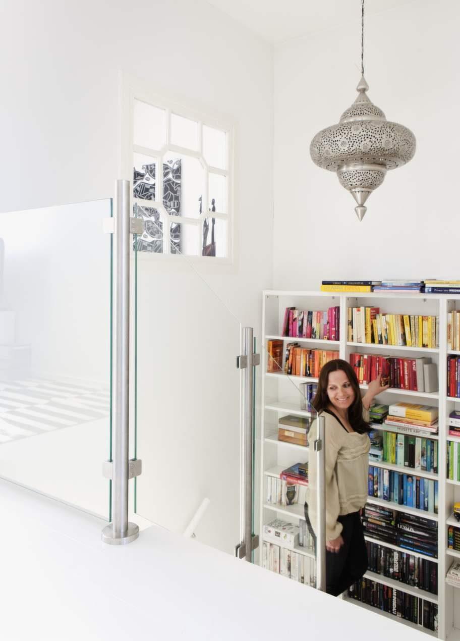 Alla bokhyllor har placerats i trappan och böckerna är ställda i färgmatchande ordning.