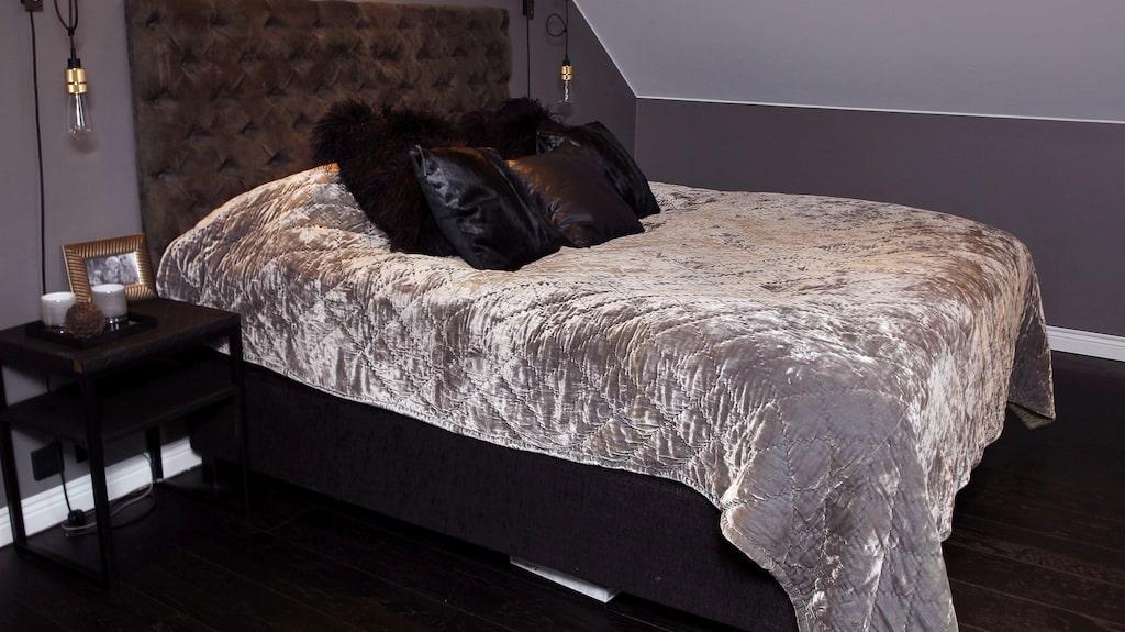 Sovrum med sängbord, lampor, överkast och kuddar från DIS Inredning.