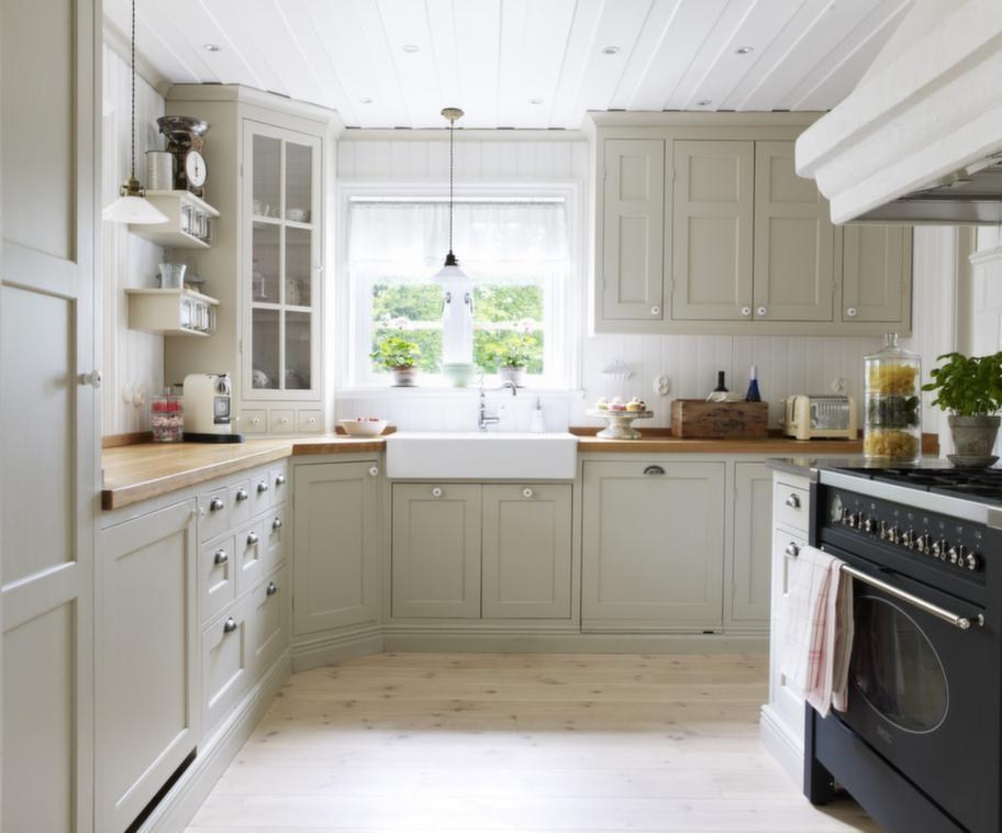 """Köket. Det platsbyggda köket är målat i en ljusgrön linoljenyans. Vitvarorna är inbyggda. """"Vi är så glada för vårt nya fina kök! En pärla och ett resultat av våra drömmar""""."""