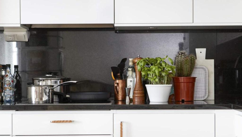 Köket går i vitt och svart. Bänkskivan i svart granit går även upp på väggen som stänkskydd.