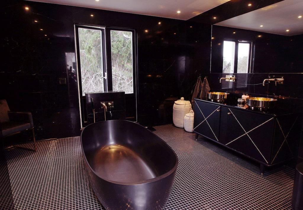 Badrummet är inrett med väggar i svart marmor och svart glasmosaik på golvet. Det mattsvarta badkaret är från Nordhem.