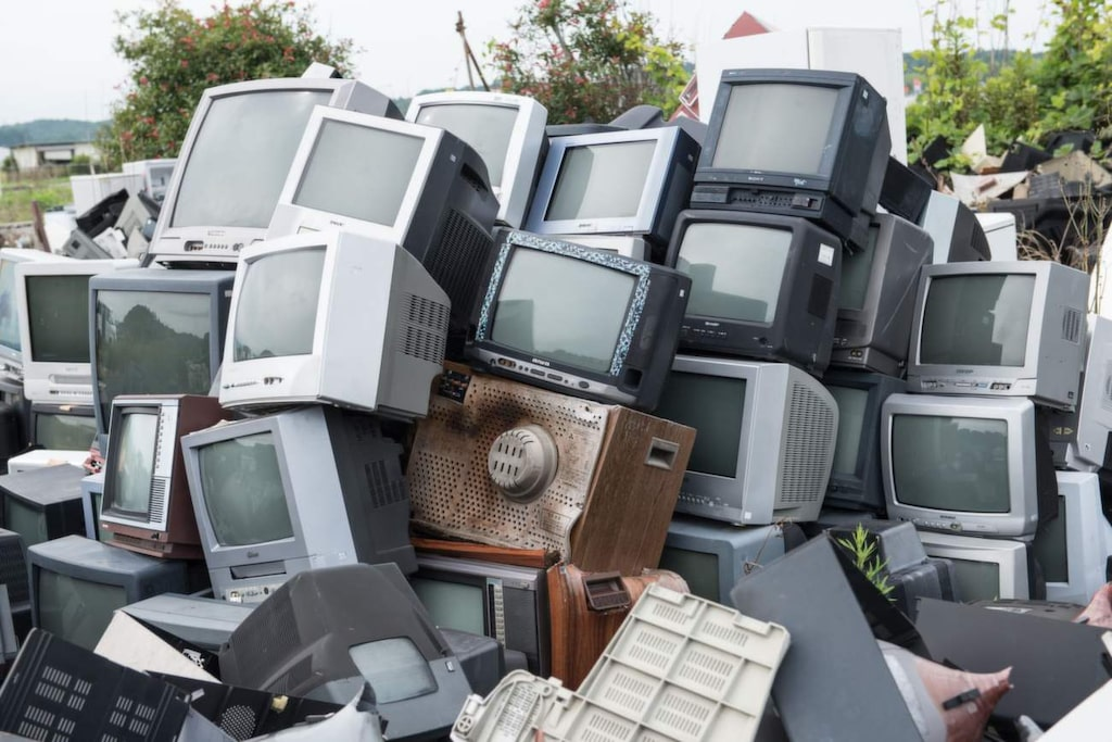 <p>Utomhus har en hög med gamla tv-apparater pallats upp.</p>