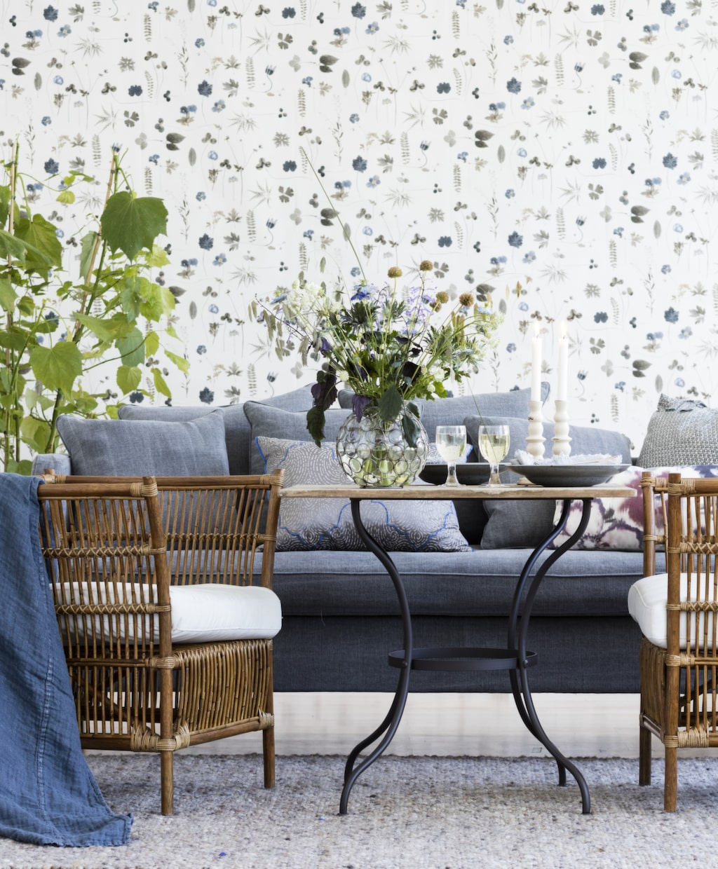 Tapetsera med somriga blommor och inred med möbler som passar lika bra ute som inne. Med vintagemöbler blir stilen fulländad.