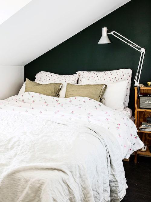 En mörk fondvägg gör sovrummet mysigt. Sängkläderna är från Ikea och prydnadskuddarna av linne är från Himla. Överkastet av linne är från Society limonta.