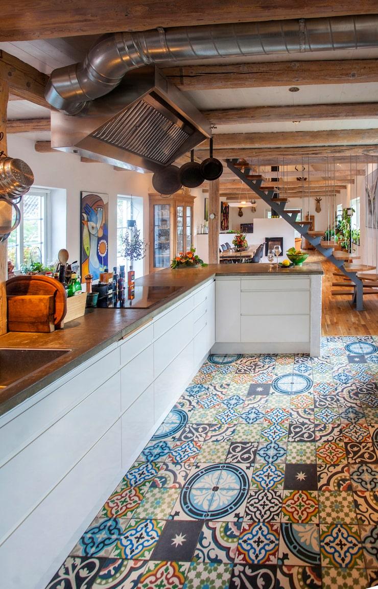 De varma tonerna i Marrakechplattorna på golvet bryter av mot den annars industriella köksinredningen. Köksinredningen är från Brösarpsköket.