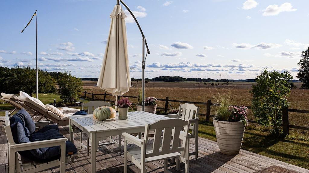 Uteplats och soldäck med vy över ängarna som rymmer både matbord och solstolar.
