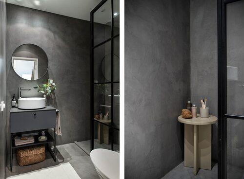 Badrummet renoverades 2019 och matchar köket med microcement på golv och väggar. Duschen gömmer sig bakom en industriglasvägg.