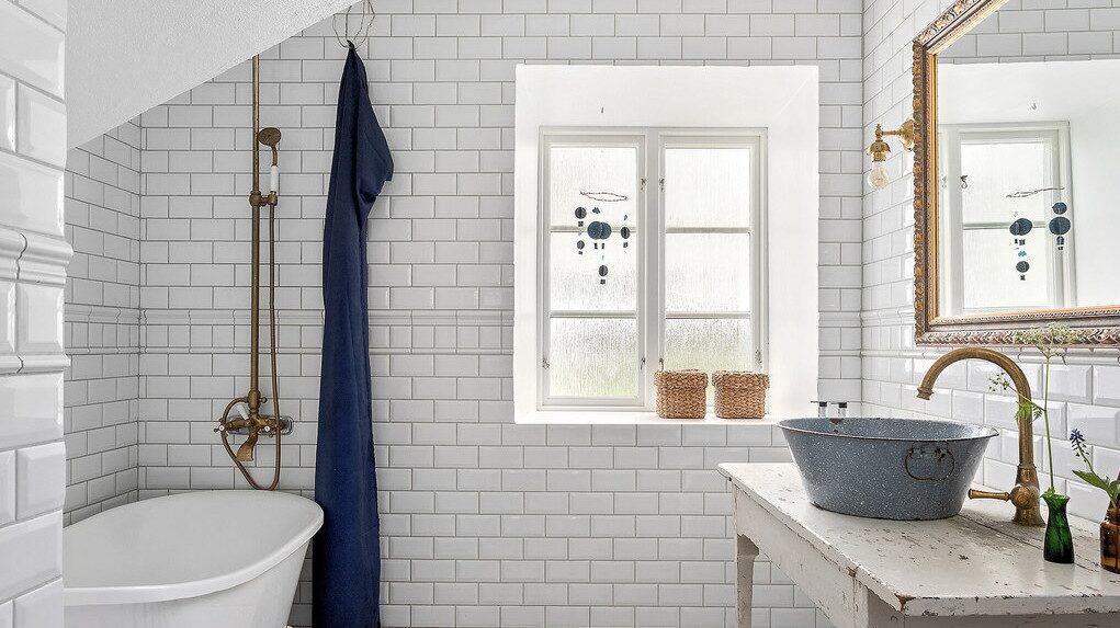 Badrummet är charmigt och ljust med vitt kakel, tess-badkar och äldre stil på handfat, dusch och kranar.