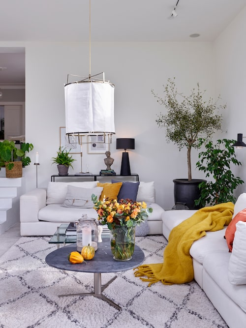 """Familjens nya """"sunroom"""" ligger några trappsteg längre ner än husets ursprungliga bottenplan. Rummen förbinds av en stilren vitmålad betongtrappa. Taklampa Malibu, Hallbergs. Orange kudde och lejongul pläd, Svanefors. Matta, Ellos."""