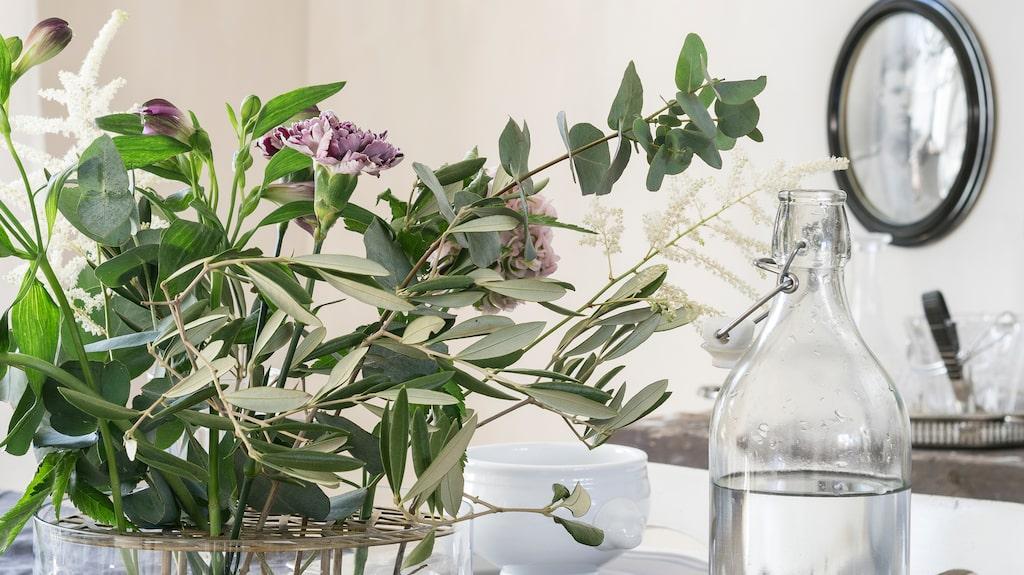 Färska blommor bryter fint av mot den mörka linneduken. Porslin och glas från Ikea.