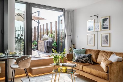 Glasade fönsterpartier mot terrassen skänker ljus till allrummet.