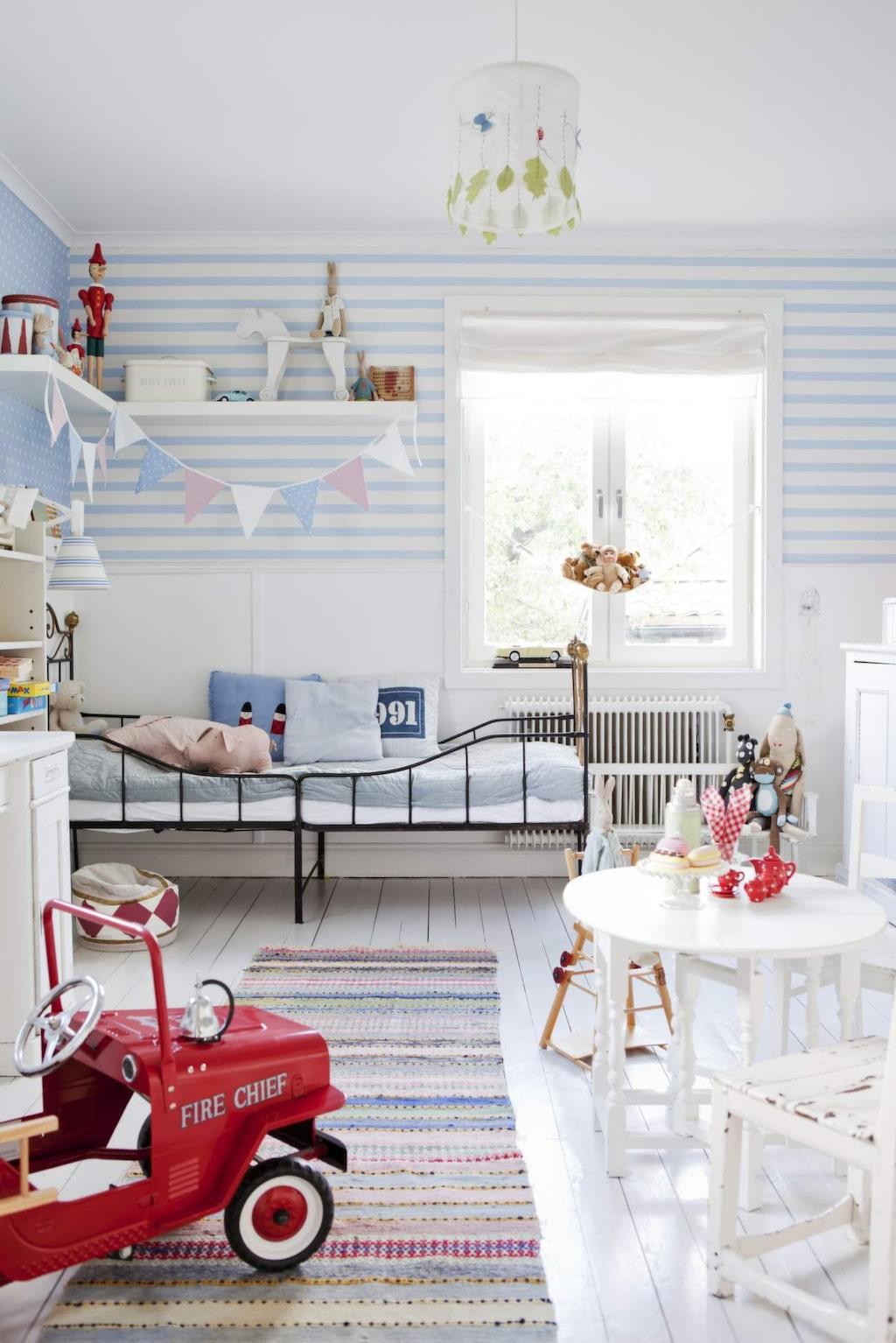 <p>Randigt på väggar och golv. Trasmatta och äldre stålsäng. Stor leksaksbil av plåt är både leksak och prydnad i rummet. <br></p>