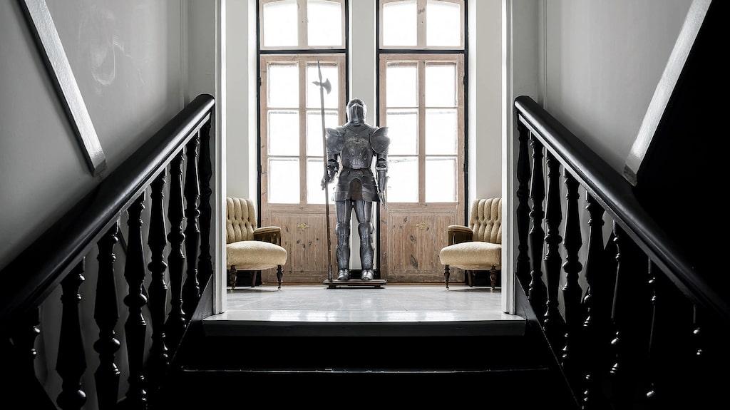 """En """"riddare"""" vakar över andra våningen vid balkongen som vetter ut mot gården."""