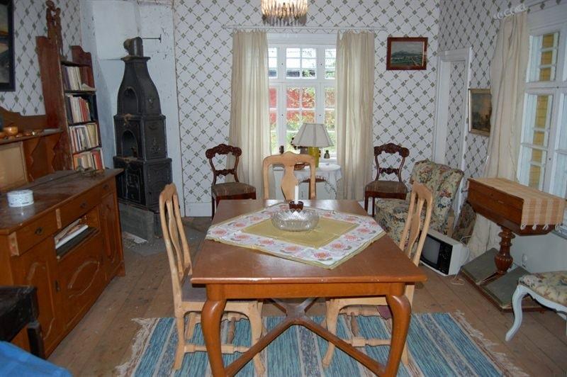 Vardagsrummet har furugolv, tapetserade väggar, målade takskivor och utgång till veranda, samt en unik kamin.