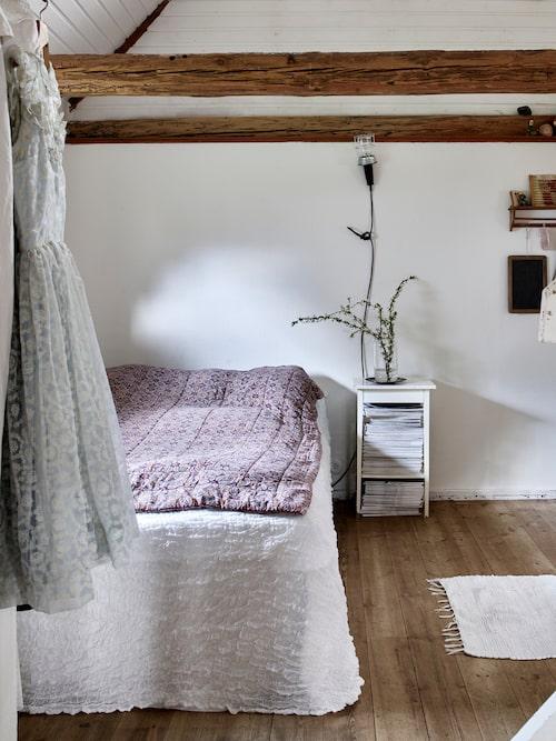 Sovrummets tak är öppet upp till nock. Vaddtäcke, loppis. Överkast, Ikea.