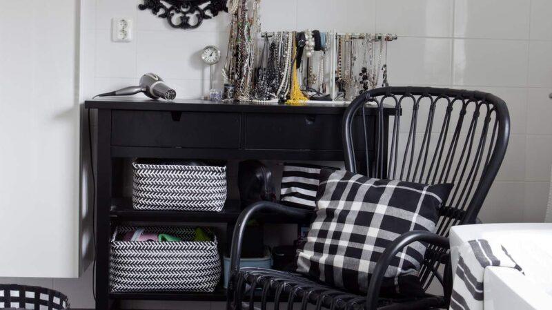 <p>Svart och vitt. Badrum med svart&nbsp; mosaikgolv och stora vita kakelplattor på väggarna. Rottingstol, sideboard och spegel Ikea.</p>
