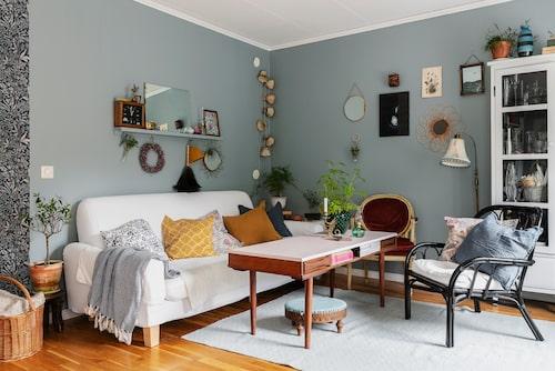 Familjens inredningsstil är en blandning av nya, ärvda och egentillverkade möbler. Golvlampan i vardagsrummet kommer från Mias mammas kafé, och lampskärmen har hon klätt om i ett kimonotyg. Väggen har de målat i kulören Bombay från Alcro. I soffan ligger kuddar från bland annat Bemz, H&M Home och Hemte