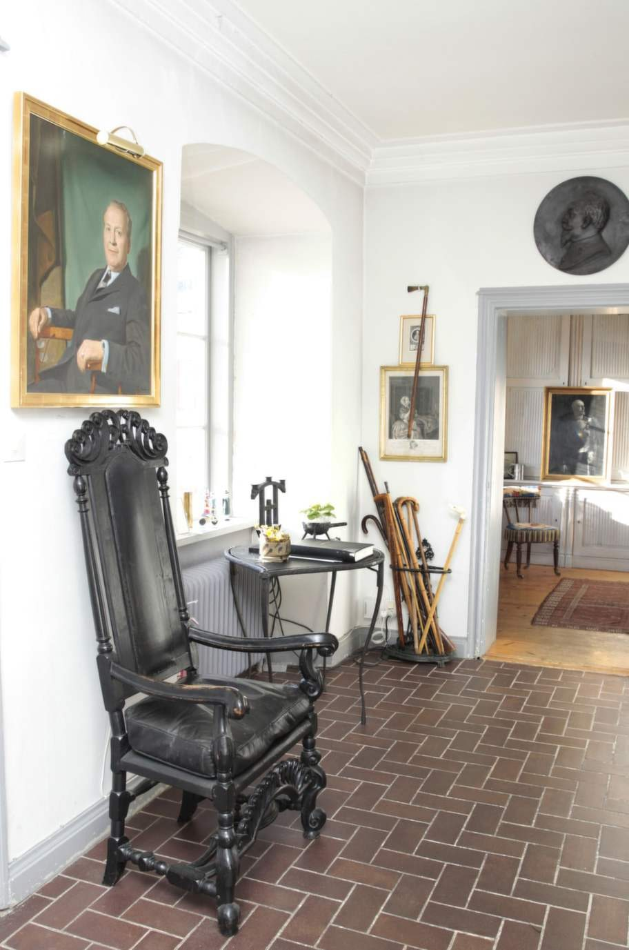 """Porträtt. I hallen tronar en barockstol under porträttet av Carl Jans morfar, Gustaf Ahlkvist, som drev """"The swedish health center"""" i Allentown, Pennsylvania. En samling spatserkäppar skymtar i hörnan."""