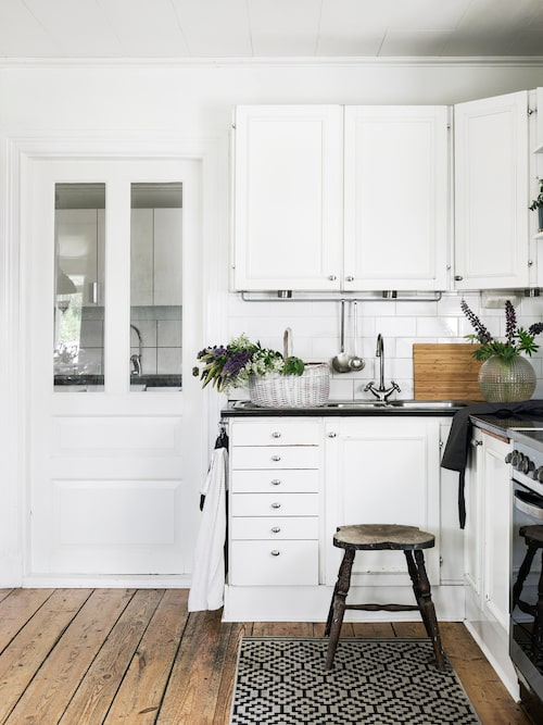 Ett köksbygge i lantlig stil var bland det första familjen tog tag i när de flyttade in. Bakom glasdörren syns tvättstugan som går i samma stil. Den nötta stolen utan ryggstöd hittade de bland bråten i ladugården.