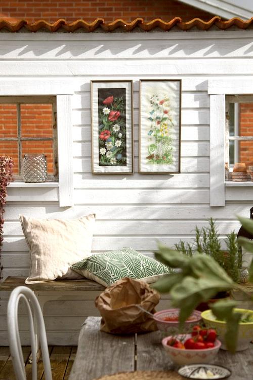 På trädgårdsaltanen har ett plank byggts för att få både vindskydd och avskärmning mot grannhuset. Små fönster i planket skapar hemtrevnad tillsammans med tavlor och kuddar.