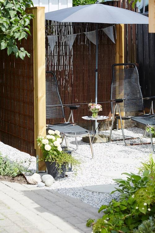 Inspirerade av japanska trädgårdar skapade Hanna och Olof sin egen lilla solhörna. Här inramat som ett rum med hjälp av pilmatta och ramar av armeringsjärn. Trampstenar i betong som Olof själv gjutit. Solstolar Spaghetti från Fiam. Kvadratiskt svart parasoll från Grythyttan.