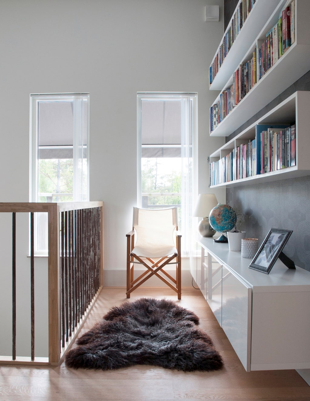 På övervåningen har familjen ett allrum. Räcket i trappen liksom den öppna bokhyllan har Jens gjort. Maries föräldrar födde upp lamm, och från dem kommer lammskinnet.