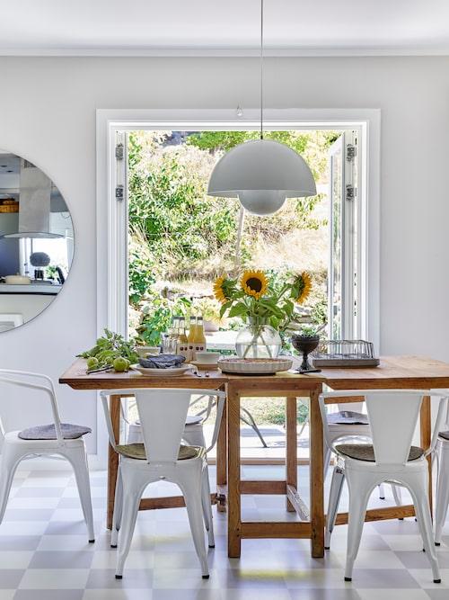Matplatsen ligger i den nybyggda delen av huset. På golvet ligger ett schackrutigt linoleumgolv som ger fin känsla åt rummet. Här har paret mixat gammal och ny inredning i en skön mix. Runt det antika slagbordet står klassiska stolar från Tolix. Över bordet hänger en antik Flower pot-lampa designad av Verner Panton. Den stora spegeln skapar djup och ger rummet en fin karaktär. Spegeln kommer från butiken Olgas hus.