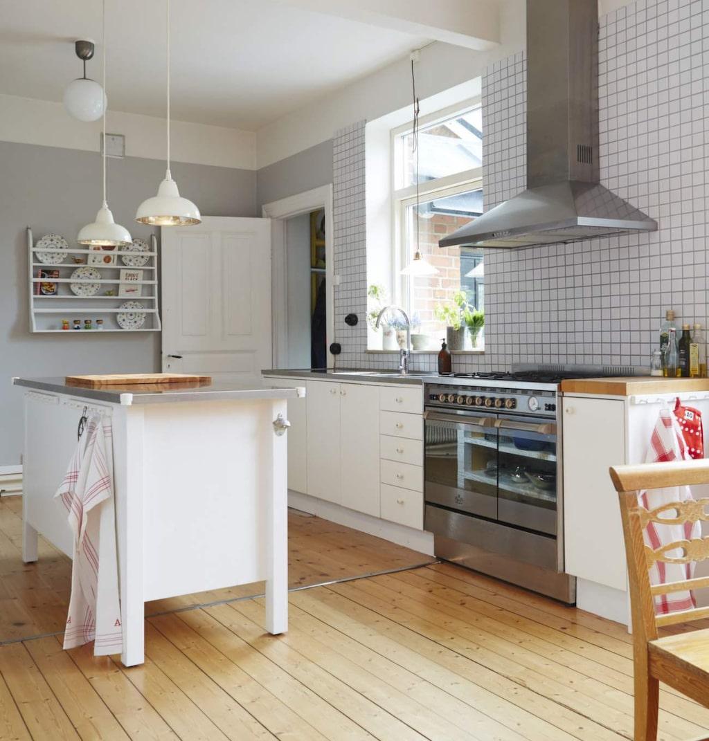 Det rymliga köket är en central plats i hemmet. Takpendlar från Slättarps gård lyser upp köksön.