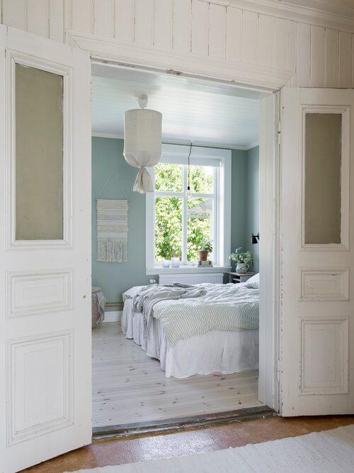 """Gamla fina pardörrar leder in till Ericas och Sebastians sovrum med vacker utsikt över villaområdet.Sovrummet har fått ett vitvaxat furugolv och nytt tak. Väggarna är målade i kulören """"Tant Johannas gröna"""" S3005-G20Y. Sängkläder, Navy Stories."""