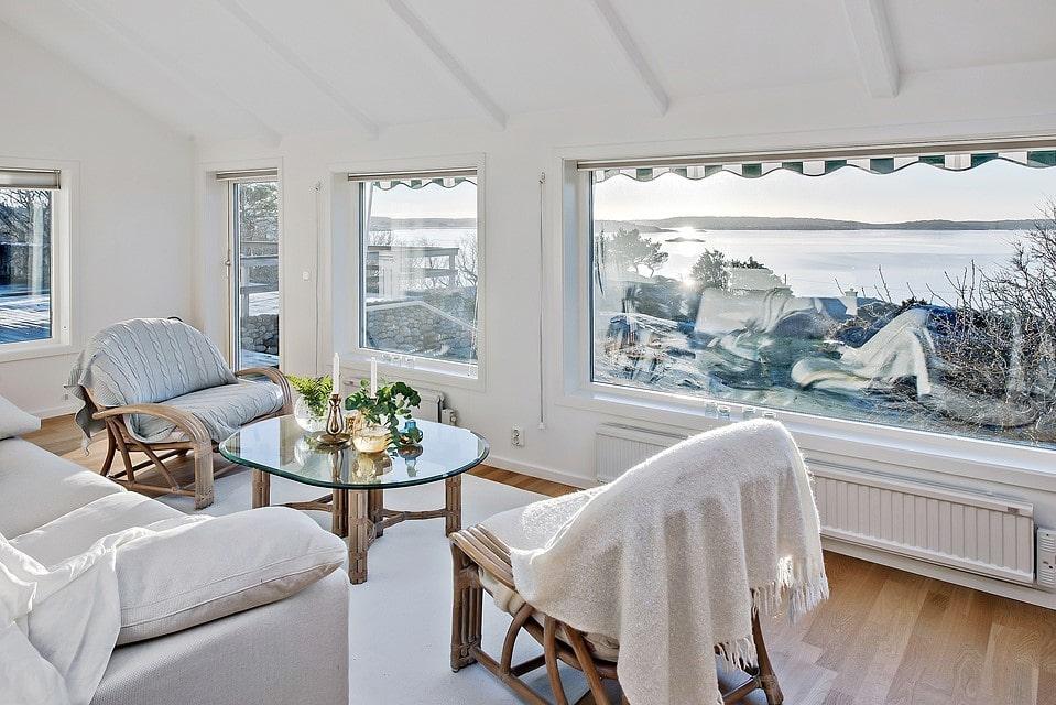 Storslagen utsikt över havet genom de stora fönstren i vardagsrummets intilliggande verandarum.