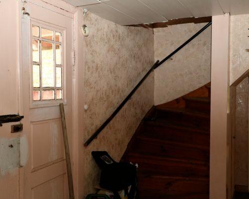 Paraddörrar med vackert spröjsade fönster leder in i huset.