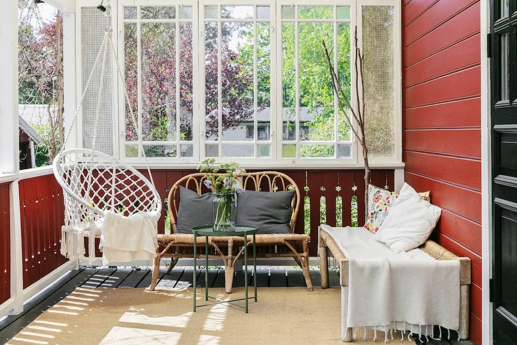 Verandan som löper längs husets baksida bjuder på plats i skuggan varma sommardagar. Hängstol från Åhléns, soffa, bord och matta från Ikea och dagbädd från Ellos.