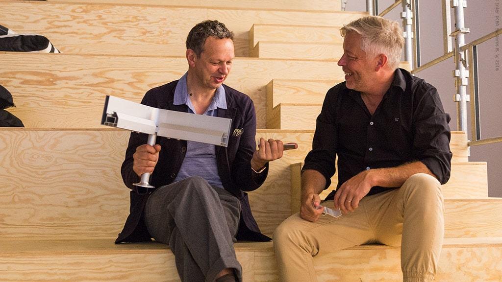 Den självlärda industridesignern Tom Dixon i samtal med designchefen på IKEA Marcus Engman. I handen håller han en del av det nyutvecklade systemet för att bygga möbler.