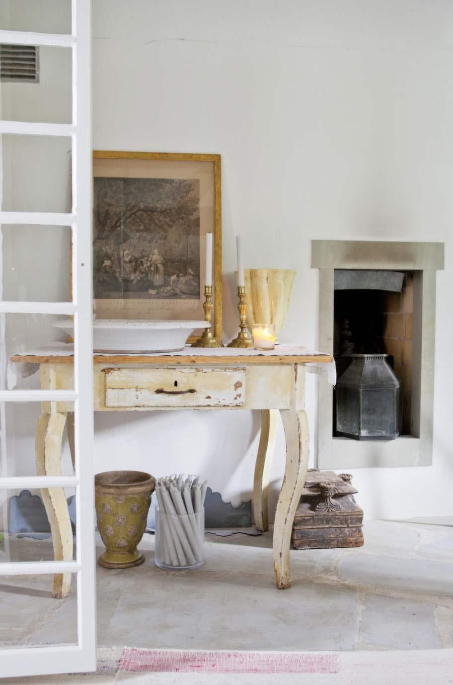 Ett vacker hörn av köket, med mässingsljusstakar och ett franskt keramikfat på ett slitet, gammalt sidobord.