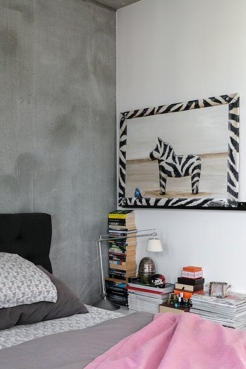 Längs väggen i sovrummet står böcker och tidningar staplade tillsammans med fina askar och nagellack. Tavla, av Jenni Berndtsson.