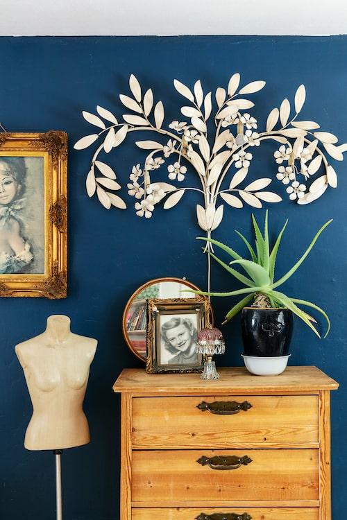 På en avlutad byrå står en vägglampa rikt dekorerad med blommor och blad. Den kommer från en av Stellas vänner som också samlar på gamla prylar. Tavlan på väggen kommer från Stellas farmor och farfar. Porträttet är ett foto av Stellas farmor som tonåring.