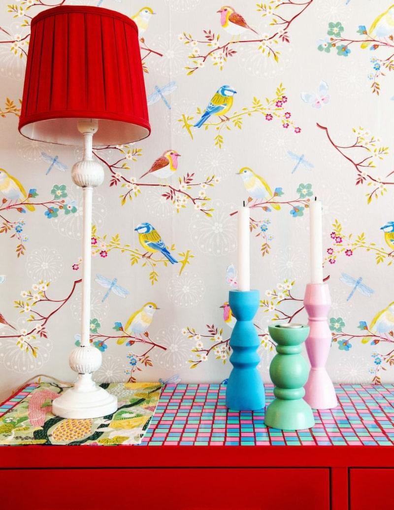 Färgkaramell. Ett plåtskåp från Ikea och serien PS, har Sara gjort till något alldeles eget och personligt. Hon har klippt ut små rutor i självhäftande kontaktplast i olika färger, som hon sedan klistrat dit. Ljusstakarna i trä har Sara köpt på loppis och målat i liknande färger som på rutorna. Tapeten kommer från PIP Studio.