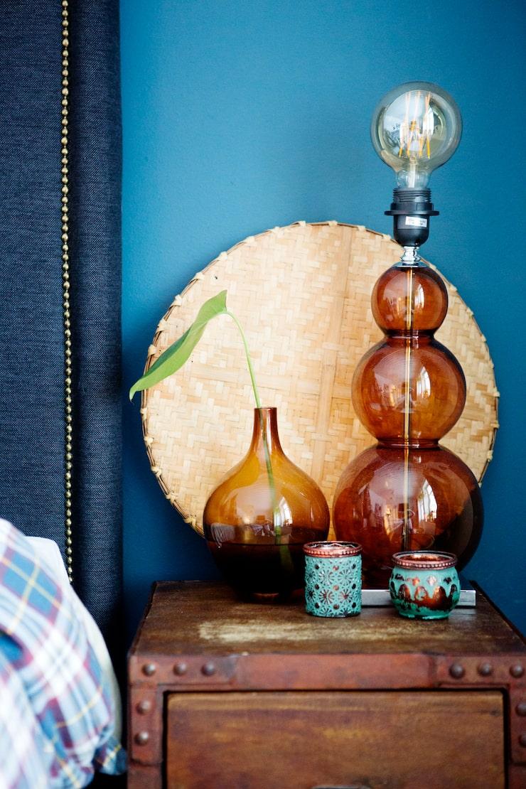 På sängbordet från My home my way står en lampa i brunt glas från Oscar & Clothilde. Vasen är ett loppisfynd.