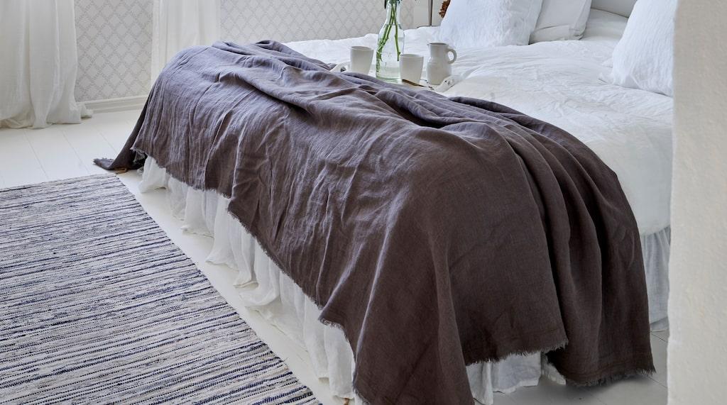 Parets sovrum har fått tak upp till nock efter renoveringen. Vita linnelakan från H&M. Mörkgrått linneöverkast från Granit. Koppar och mjölkkanna från Höganäs. Trasmatta, Ikea. Tapeten är Trellis leaves ur Borås tapeters kollektion Falsterbo II.