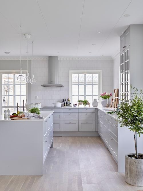 Familjen har valt att ha fler fönster i köket än det var på originalritningen. De älskar ljusinsläppet som de ger. På grund av alla fönster slopade de överskåp så att ingenting stoppar ljusflödet, men för att rama in köket valde de ändå att sätta in ett överskåp som går från bänkskivan uppåt. Det har blivit en klar favorit i köket. Kök från HTH, fläkt, Fjäråskupan, taklampor, Muuto, bubblig skål och urna, Jotex.