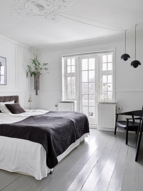 I parets sovrum har de försökt skapa en hotellkänsla. Golvet är målat i en mellangrå nyans för att ge rummet ett djup. Sänggaveln kommer från Atelier Graae och överkasten kommer från C'est Bon.