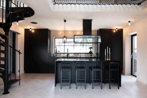 Trappan till övervåningen är, förutom stommen på huset, det enda som är kvar av den gamla 40-talsvillan. Här köket med köksö, allt i svart.